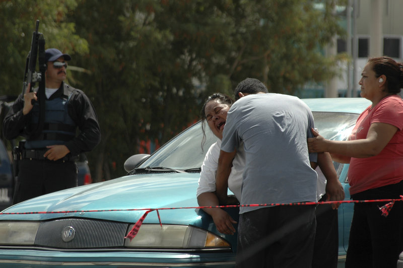 A distraught woman is consoled Thursday at the site where her son was killed by gunmen in Ciudad Juarez, Mexico.