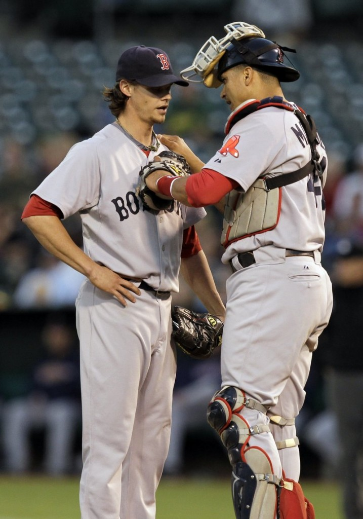 Red Sox pitcher Clay Buchholz and catcher Victor Martinez chat at the mound after Oakland's Kurt Suzuki's two-run double in the first Friday night.