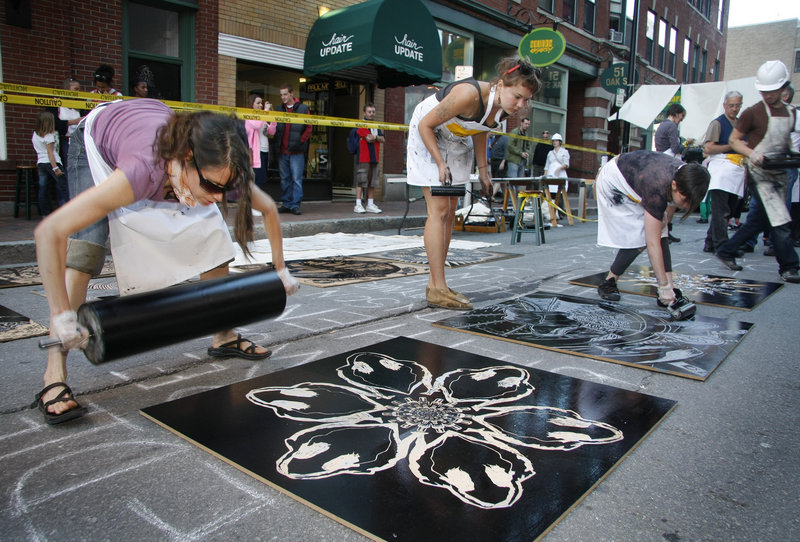 Carrie Scanga of Brunswick, left, and Irina Skornyakova of Portland, center, roll ink onto giant woodblocks created by local artists during the Space Gallery Block Party on Congress Street in Portland on Saturday. The woodblocks were then printed on bed-sheet-sized pieces of canvas with a giant steamroller provided by Pickwick Independent Press.