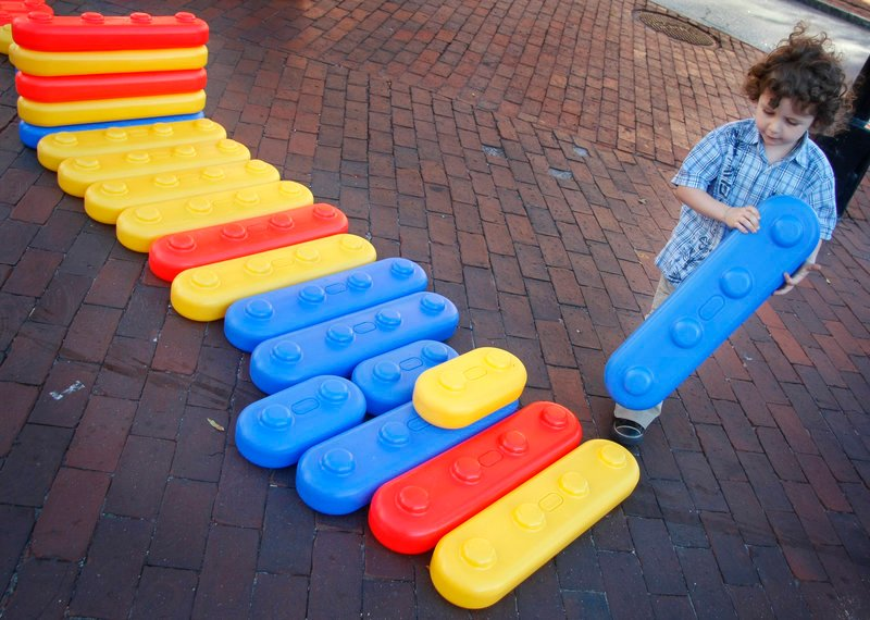 Oisin Malakie McCullough, 3, of Portland gets creative with giant blocks outside The Children's Museum & Theatre of Maine during the Space Gallery Block Party on Congress Street in Portland on Saturday.