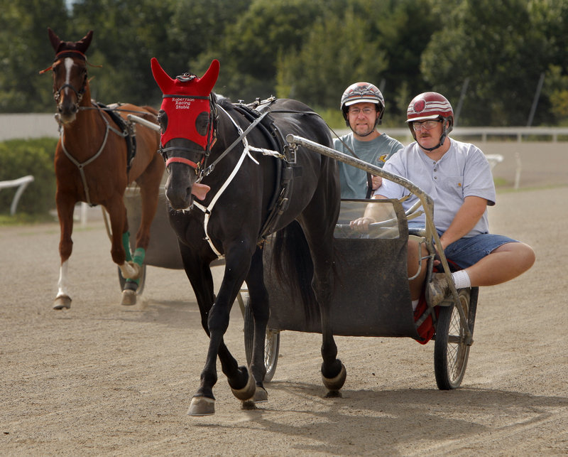 Reporter Ray Routhier, left, drives a jog cart around the track at Scarborough Downs with trainer Dick Robertson Jr.