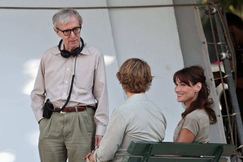 """Carla Bruni-Sarkozy, the first lady of France, talks with director Woody Allen, left, and American actor Owen Wilson during the filming of """"Midnight in Paris"""" on July 28 in Paris. Bruni-Sarkozy plays a museum tour guide in the movie."""