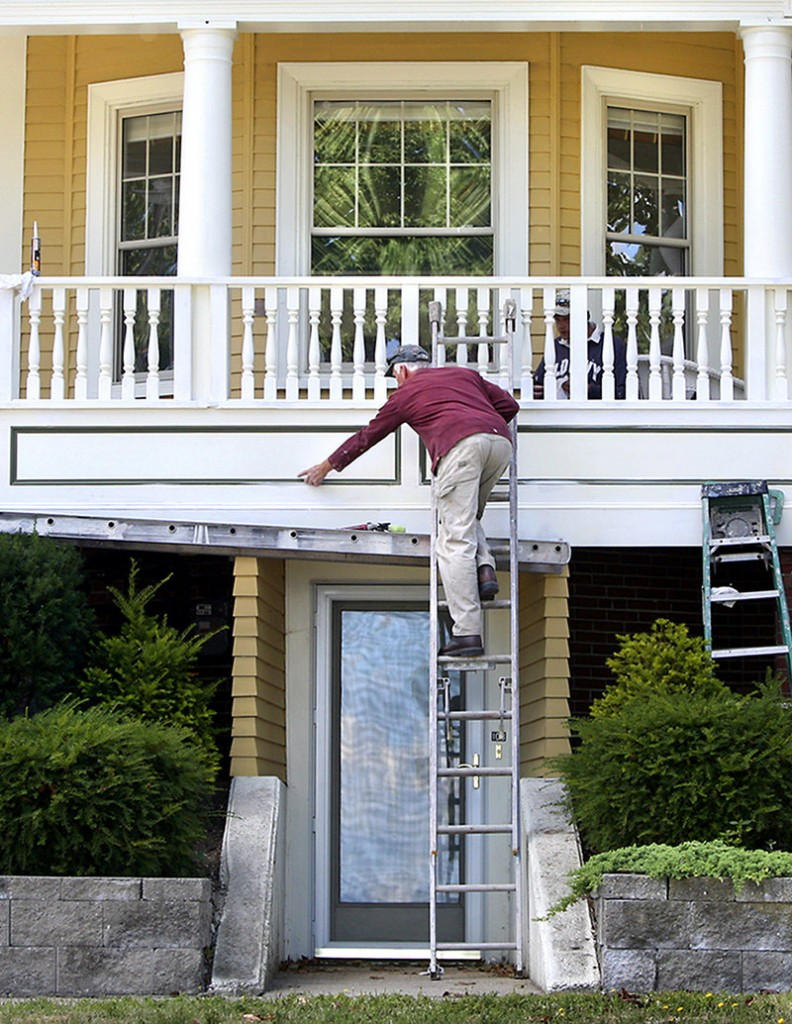 Rob May of Classic Painting and Wall Covering smooths out the caulking on a wraparound porch Tuesday at a house on Munjoy Hill in Portland. May said he is scraping, sanding and caulking the front of the home and expects to finish the work by the end of the month.