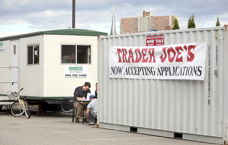 Ryan Hall of Portland fills out a job application Thursday outside the new Trader Joe's store on Marginal Way in Portland. The company hopes to open the store by the end of the year.