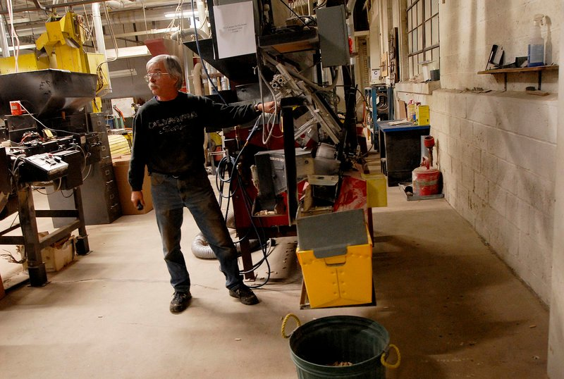 Longtime employee Foster Davis demonstrates an automatic sorter at the Saunders Brothers mill in Locke Mills on Monday.