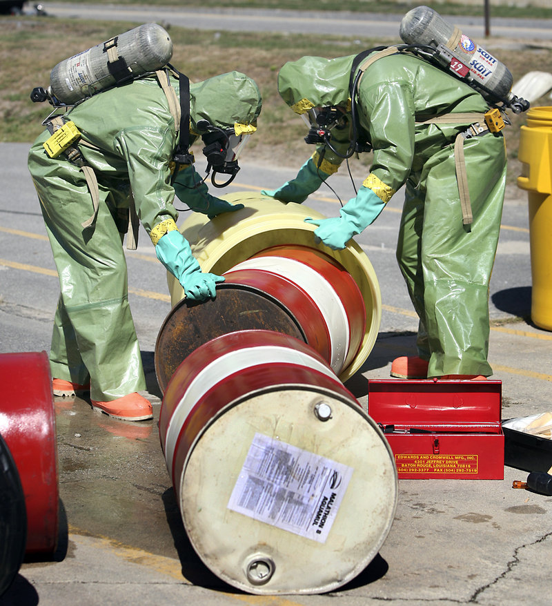 Members of Portland's Fire Department move a drum of potentially hazardous material into a containment barrel during a Weapons of Mass Destruction drill Thursday morning on Read Street. During the exercise, crews responded as if drums of pesticide were leaking after a truck crash.