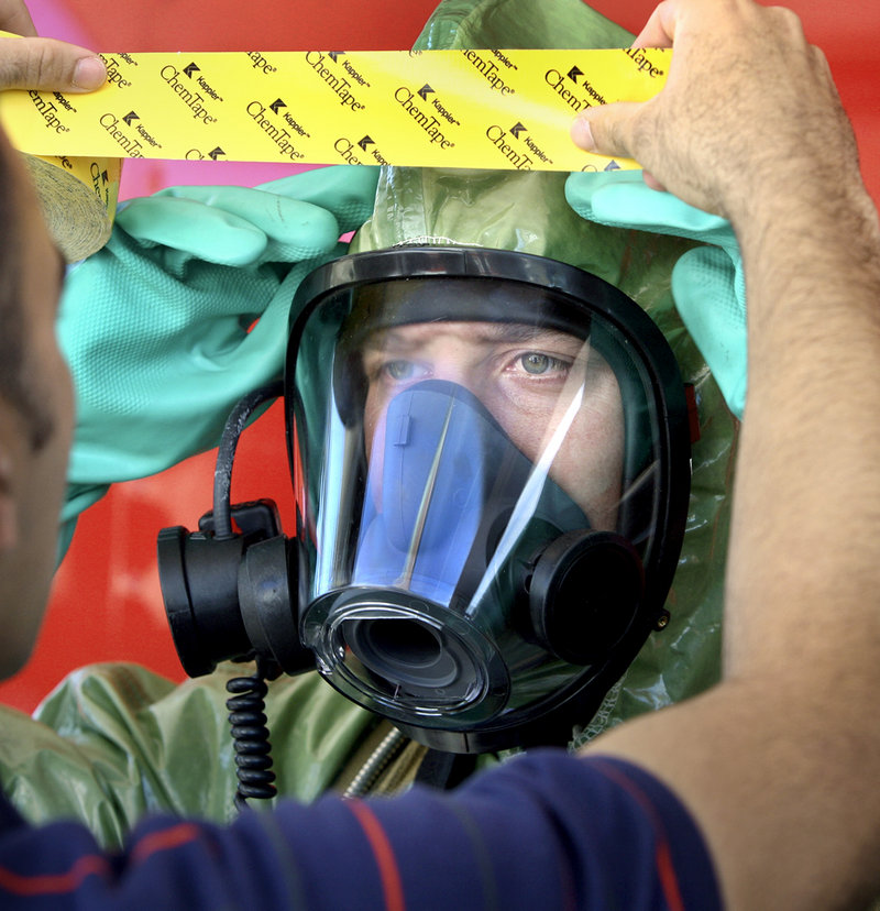 Police officer Dan Townsend places a piece of tape on the hazardous material suit of firefighter Phil LaRou, as LaRou prepares to contain a spill during Thursday's Weapons of Mass Destruction team exercise on Read Street.