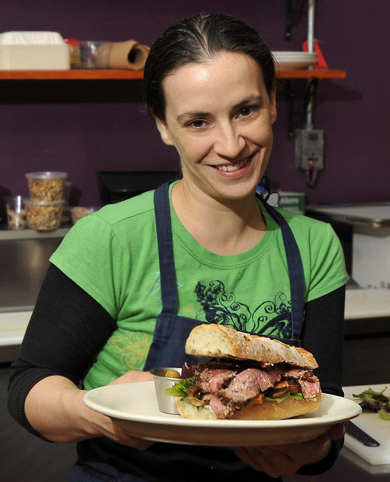Owner Melissa Coriaty shows off her jerked flank steak sandwich.
