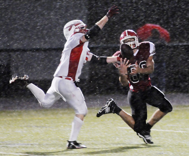 Justin Carlson, left, of Sanford tips a pass away from Scarborough's Mike Cyr, but pass interference on the play set up the Red Storm's first TD in a 14-0 win Thursday.