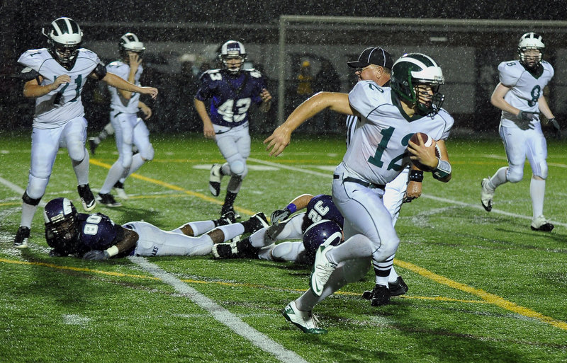 Bonny Eagle quarterback Matt Rollins runs away from the Deering defense during the first half of Thursday's game at Memorial Field. Rollins rushed for 195 yards and two touchdowns, leading the Scots to a 34-12 victory.