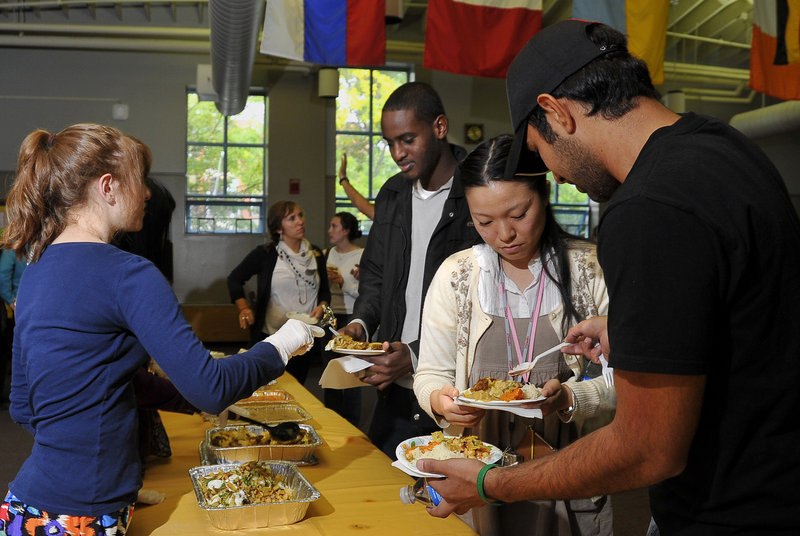 Volunteers from USM serve a variety of Middle Eastern and Indian food at the Eid celebration to mark the end of Ramadan, an event held at the university's Woodbury Campus Center in Portland on Friday. Zag Alanjari, right, spoons a special sauce over the plate of Fumino Shiobara as Guled Ilmi, center, is served by another volunteer.
