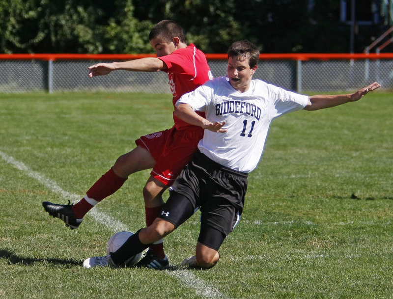 Michael Lachance of Biddeford attempts to knock the ball away from Nate Fox of South Portland during their Southern Maine Activities Association soccer game Saturday at Biddeford. South Portland earned a 5-2 victory.