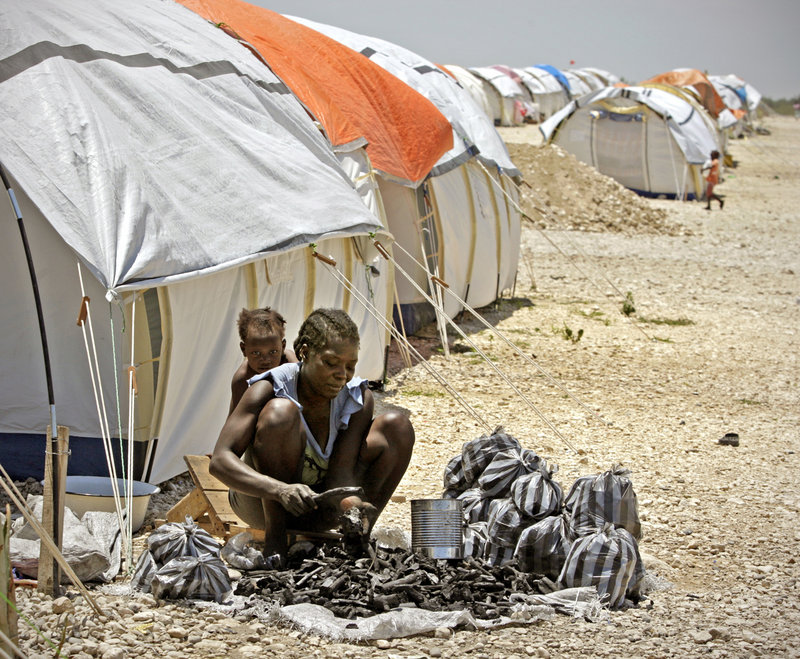 A woman bags charcoal at the Corail-Cesselesse emergency relocation camp in Port-au-Prince, Haiti, where more than 5,000 victims of the catastrophic Jan. 12 earthquake live in tents. She sells the charcoal to camp residents for cooking.