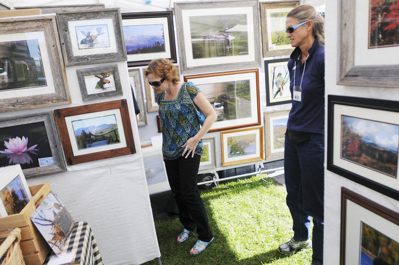 Angel Lorom of Bath looks over the photography of Johnna Haskell, right, of Carrabassett Valley.