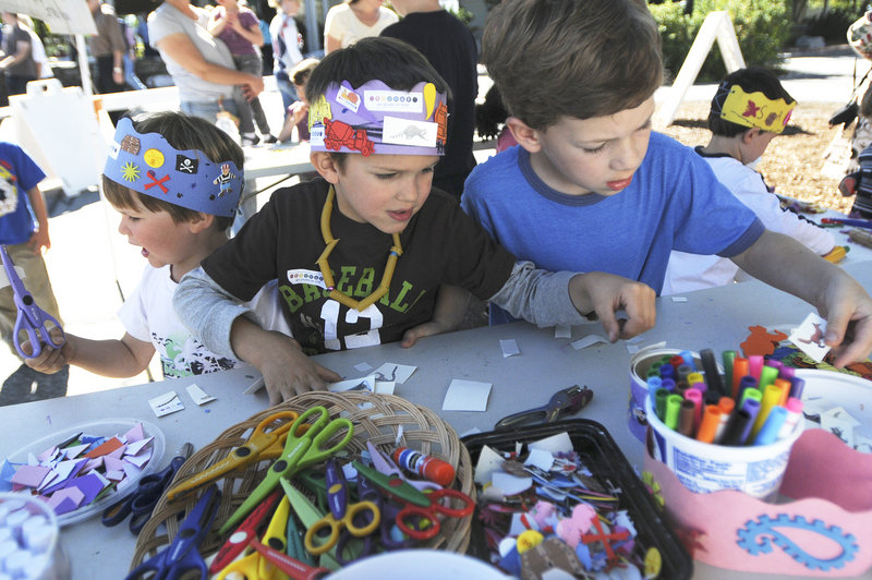 Cooper Jacobs, 3, of Freeport, Kaiden Jacobs, 5, of Freeport, and Luke Vazdauskas, 5, of Brunswick make the most of the festival by creating their own artwork.
