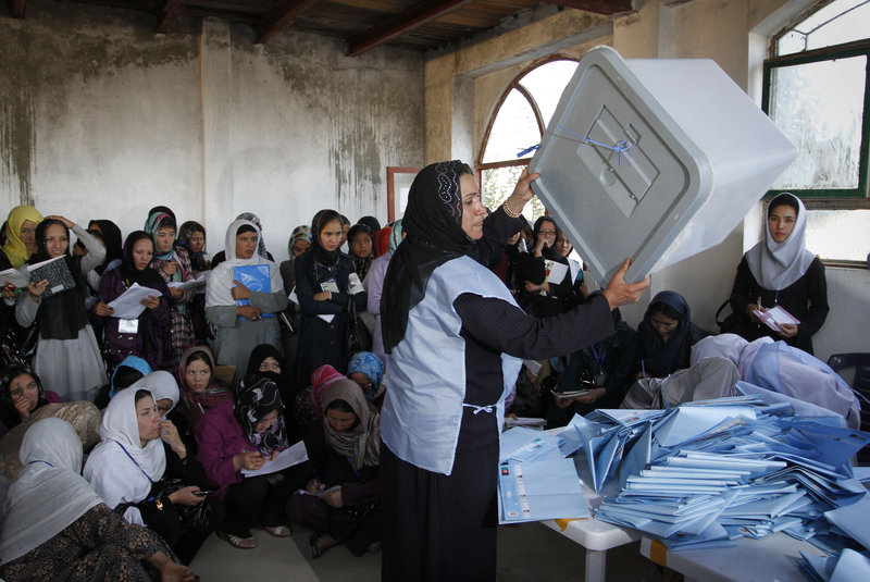 An Afghan election worker displays an empty ballot box to polling agents during counting of ballot papers at a polling station during the parliamentary election in Kabul on Saturday.