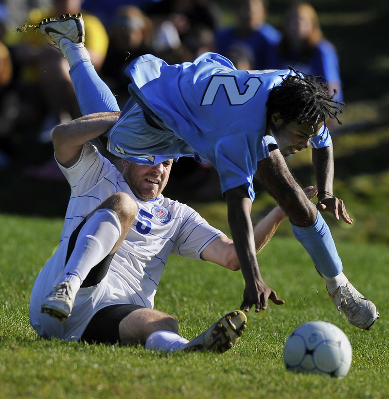 Brandon Noltkamper, bottom, of St. Joseph's trips up Lasell's Javon Scott as they battle for a loose ball Saturday during a men's soccer game at Standish. Lasell won, 3-0.