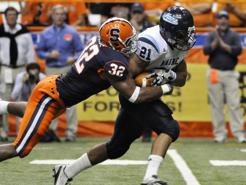 Maine's Jared Turcotte gets hauled down by Syracuse's Doug Hogue during Saturday's game. Turcotte ran for 34 yards in the first half as Maine stayed within three points.