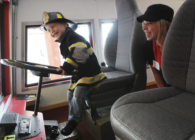 Braiden Edens, 3, of Lisbon plays in the fire truck as his mother Ashley Edens looks on during the Neonatal Intensive Care Unit Reunion of Maine Medical Center, held at the Children's Museum and Theatre of Maine in Portland on Sunday.
