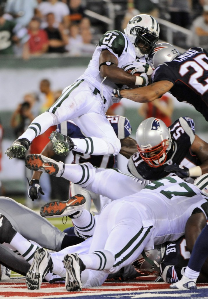 Jets running back LaDainian Tomlinson jumps over a pile of players for a first down late in the game on Sunday at New Meadowlands Stadium in East Rutherford, N.J.