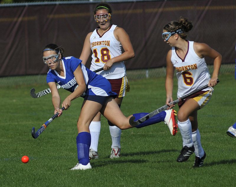 Jenn Davis of Kennebunk drives the ball ahead of Thornton Academy defenders Morgan Dube, right, and Katie Campisi during their SMAA field hockey game Wednesday at Saco. Kennebunk improved to 4-1-1 and Thornton fell to 4-2-1 as the Rams won, 3-0.