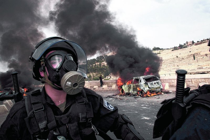 An Israeli police officer wearing a gas mask walks past a car set on fire by Palestinian rioters Wednesday outside Jeru-salem's Old City. Violence erupted after a Palestinian laborer was killed by a security guard watching over Jewish families.