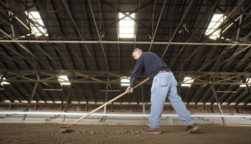 Jim Hawkes of Albion rakes stones out of the pulling ring at the Cumberland Fairgrounds on Friday. The fair opens Sunday and runs through Oct. 2. The first event in the ring is the 3700 and under oxen 6-foot pull, starting at 9 a.m. Sunday.