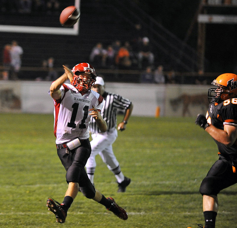 Jack Adams, who passed for 318 yards and three touchdowns Friday night for Scarborough, sends the ball downfield while being pursued by Cody Chaloult of Biddeford. Scarborough came away with a 21-9 victory.