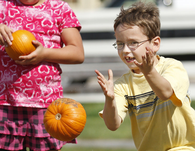 Oliver Robidoux, 6, of Waterboro bowls a pumpkin in one of the games during the Punkinfiddle festival in Wells.