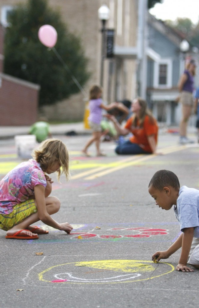 Taja Foster, 10, left, and Derek Pascal, 6, are immersed in their art on Adams Street Saturday, during the community mural project sponsored by the Heart of Biddeford organization.