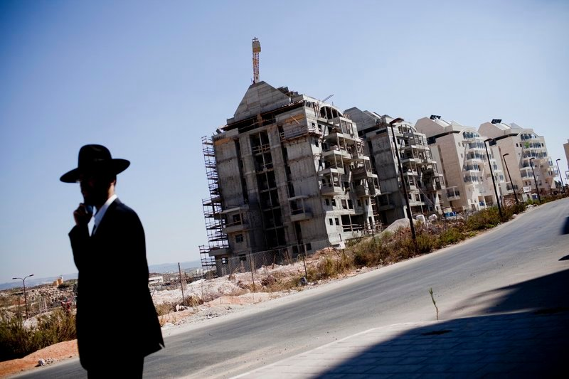 An Ultra-Orthodox Jewish settler walks near a construction site in the West Bank Jewish settlement of Modiin Ilit. Israel imposed the 10-month moratorium in a gesture to get the Palestinians to agree to peace talks.
