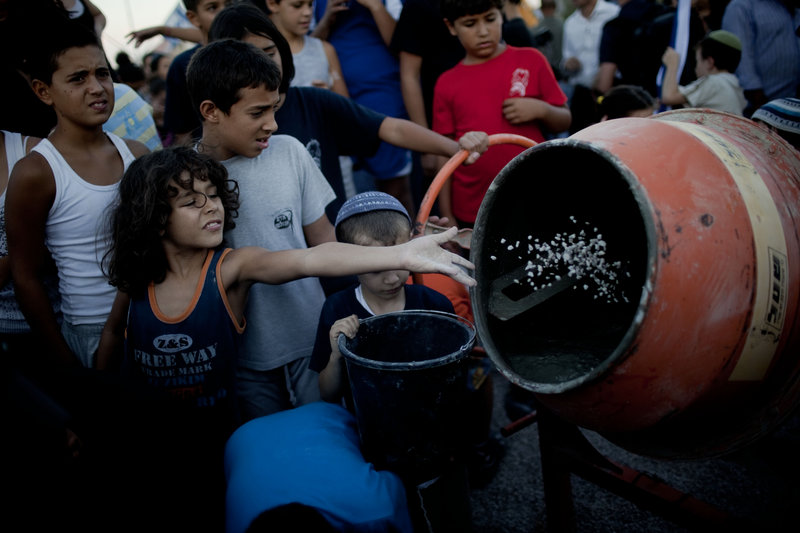Jewish children throw material into a cement mixer during a symbolic ceremony to renew construction in the West Bank, in the Jewish settlement of Adam, near Ramallah, this month.