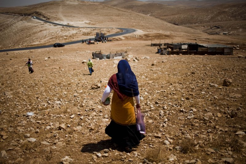 Settlers walk toward the West Bank town of Jericho, through the Jordan valley, last month. Many religious settlers believe that all of the land promised to Jews in the Bible, including what is now the West Bank, belongs to them.