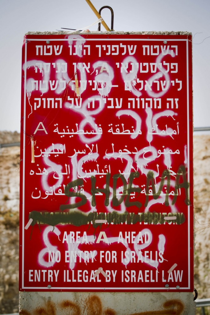 Graffiti sprayed on top of a road sign forbidding Israelis from traveling in Palestinian territory last week reads the state of Israel degraded.