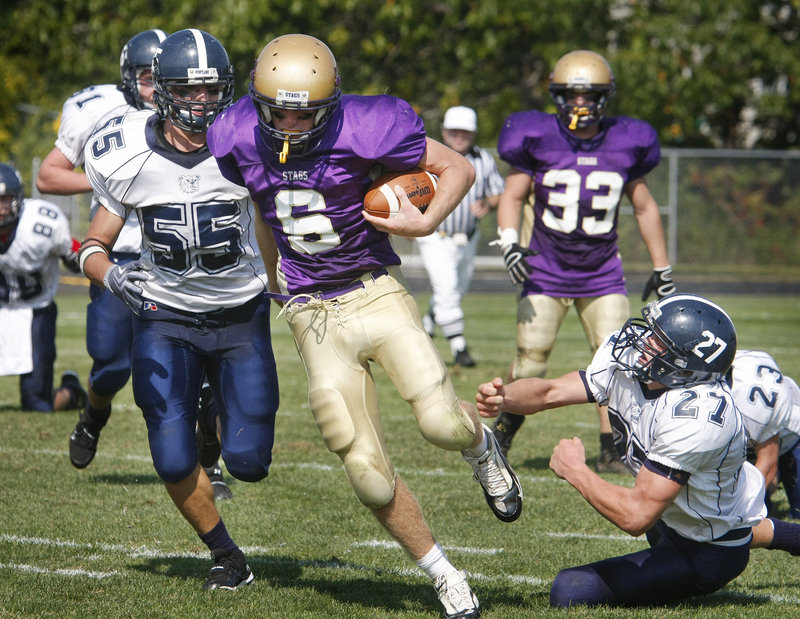 Cheverus quarterback Peter Gwilym breaks away from Max Heller, left, and Caleb Kenney of Portland during a second-half run Saturday in their Western Class A game at Cheverus High.