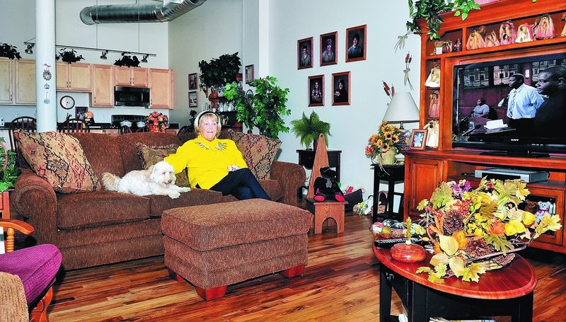"""Peggy Jason relaxes in her apartment in the Hathaway building in Waterville with her dog Buffy. Jason, who worked in the Hathaway mill for 23 years on the same floor as her studio, said, """"I love living here. I feel safe and secure."""""""