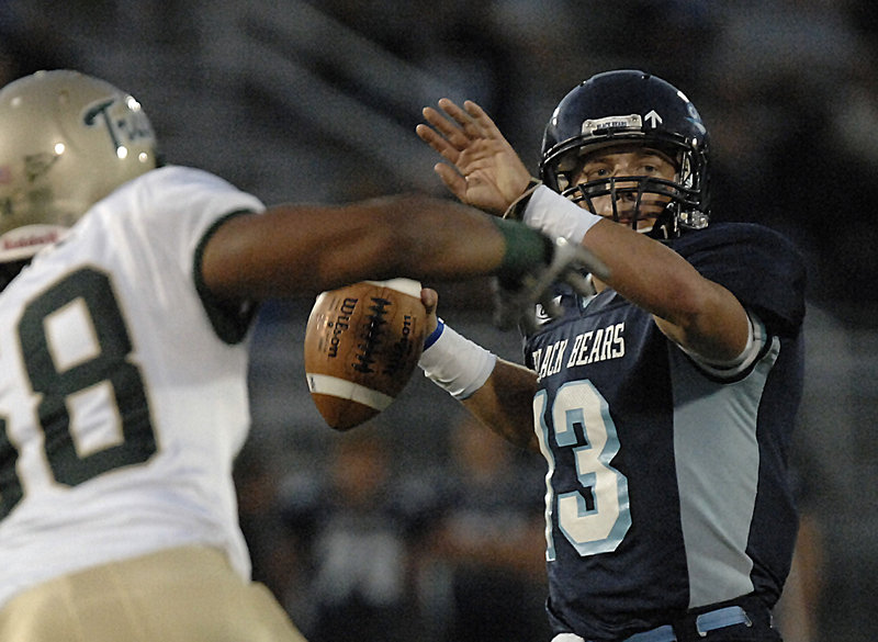 Maine quarterback Warren Smith looks to throw under pressure from William & Mary defensive lineman Bryan Stinnie in the first half Saturday night. Smith helped give the Black Bears a 14-3 lead before the Tribe rallied for a 24-21 win.