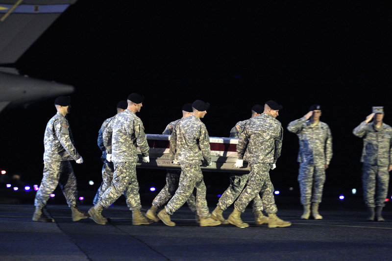 An Army team carries the transfer case containing the remains of Army Pfc. Clinton E. Springer II upon arrival at Dover Air Force Base in Delaware on Sunday.