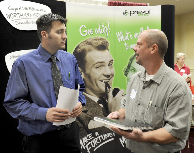 Jason Izzard, left, with Preval Direct, talks to Steve Kibler of Augusta on Tuesday during a career fair at the Italian Heritage Center in Portland. About 800 job hunters showed up for the event.