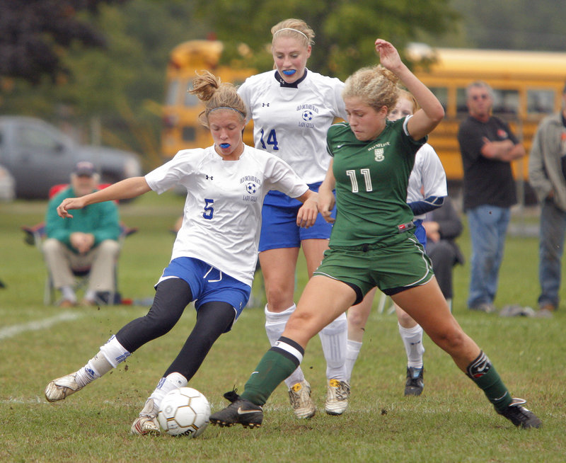 Anna Foss of Old Orchard Beach, left, and Elizabeth Berrang of Waynflete try to gain control of the ball Tuesday during Waynflete's 1-0 victory. Behind them is Katie Hatch of Old Orchard Beach.