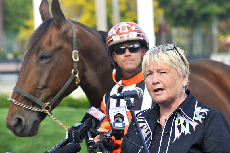 Biddeford Mayor Joanne Twomey speaks in favor of a racino complex Wednesday at Mechanics Park. At rear is harness racer Drew Campbell.