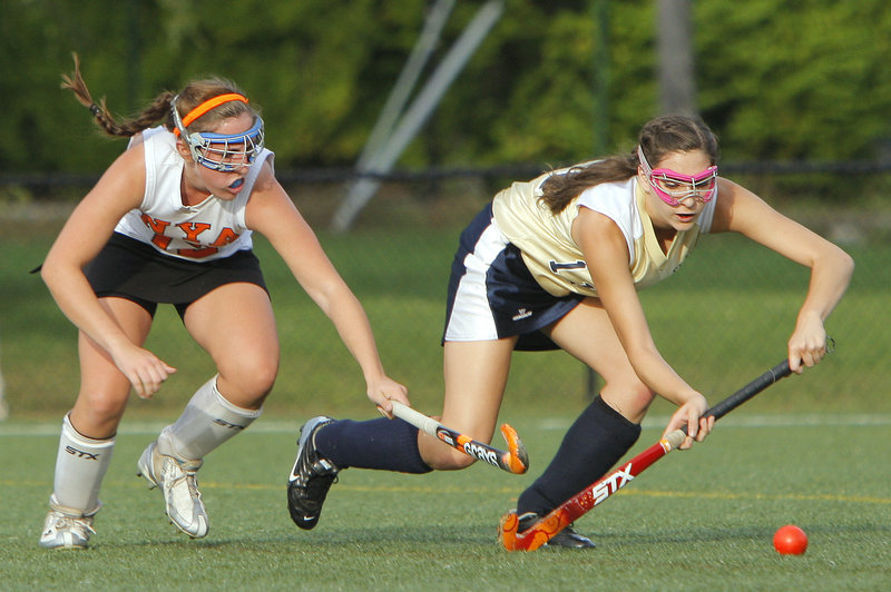 Gregory Rec/Staff Photographer Megan Fortier of North Yarmouth Academy, left, challenges Ashleigh Roberts of Traip Academy for the ball Wednesday during the first half of their Western Maine Conference field hockey game at Yarmouth. North Yarmouth Academy won, 9-1.