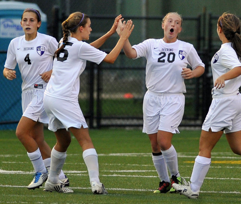 Deering freshman Alexis Elowitch, 20, receives a high-five from Georgia Hutchins after scoring the first-half goal Wednesday that gave the Rams a 1-0 victory at home against McAuley. Edie Pallozzi, left, and Tina Merrill, right, also were part of the celebration.