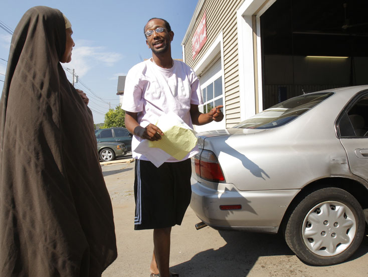 Ali Ali talks with a woman Thursday at the auto repair shop opening on St. John Street in Portland. It's believed to be the first such business in Maine owned by African immigrants, and it will specialize in serving that community.