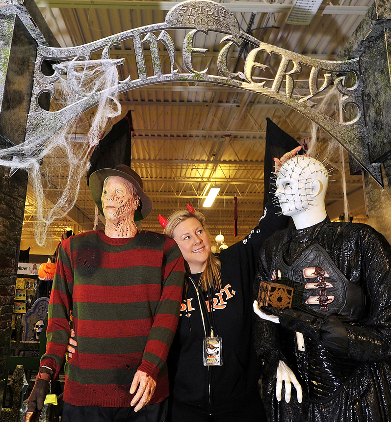 retailer deede dunbar stands between costumes of freddy krueger and pinhead at the spirit halloween store - Halloween Stores Portland Or