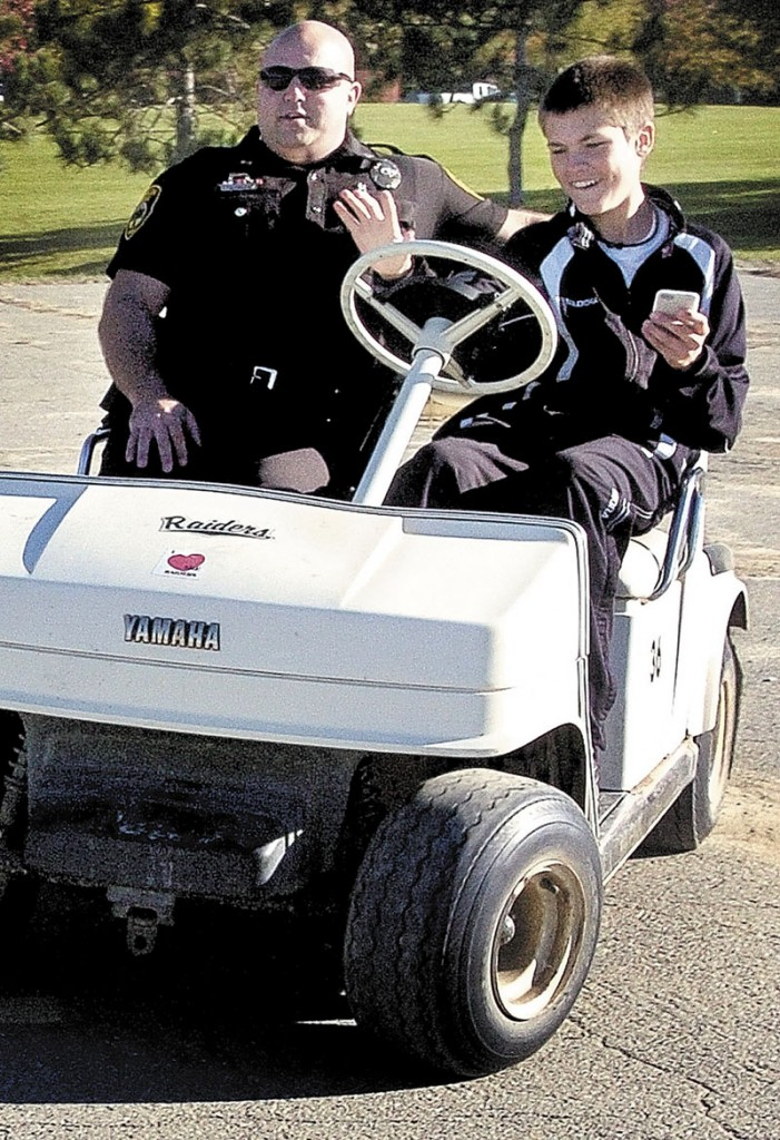 Logan Vashon, a 14-year-old freshman at Winslow High School, attempts to drive a golf cart while texting on a cell phone Wednesday morning in a parking lot near the elementary school. Sitting beside Vashon is Winslow police officer Joshua Veilleux, who discussed with students the dangers of texting while driving.