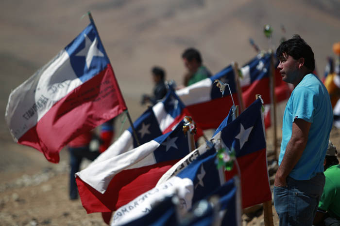 Luis Acuna, brother of trapped miner Claudio Acuna, one of the 33 trapped miners, stands next to Chilean flags today at the San Jose Mine, near Copiapo, Chile.
