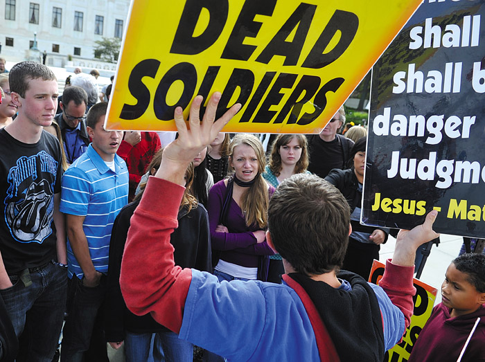 Megan Matteson, center, confronts Jacob Phelps, of Westboro Baptist Church, outside the U.S. Supreme Court Wednesday. Supreme Court justices are pondering the vexing question of whether the father of a dead Marine should win his lawsuit against a fundamentalist church group that picketed his son's funeral.