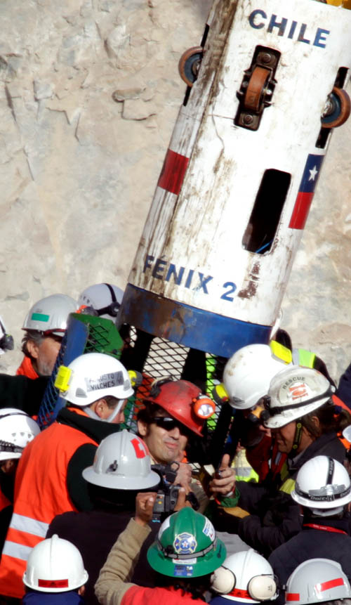 Miner Alex Vega Salazar, center, gives a thumbs up after emerging from the capsule that brought him to the surface today from the collapsed San Jose gold and copper mine.