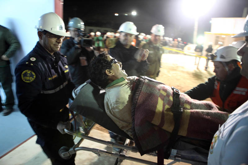 In this photo released by the Chilean government, miner Juan Illanes is carried away on a stretcher after being rescued from the mine today.